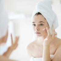 Female applying moisturizing cream after bath