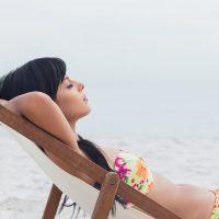 Beautiful woman sleeping on deck chair on beach
