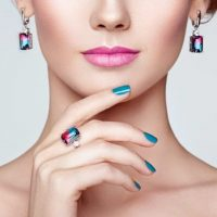 Portrait beautiful woman with jewelry. Model girl with blue manicure on nails. Beauty and Accessories. Pink lipstick